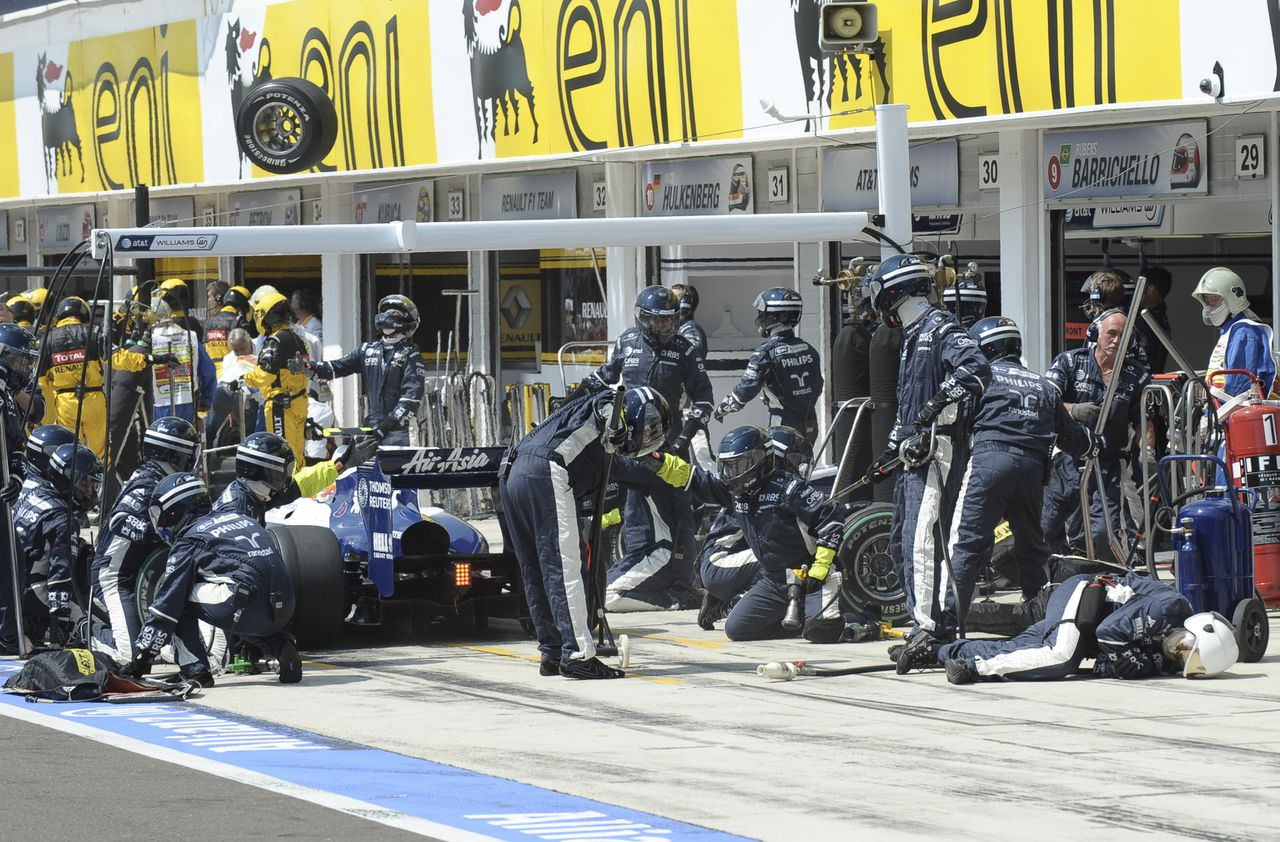 Een mechanicien ligt lichtgewond op de grond na geraakt te zijn door een achterwiel van coureur Nico Rosberg in de pitstraat. Foto AP Williams Formula One team mechanic Nigel Hope, right, lies on the ground after being hit by a wheel, top left, that came off the car of German driver Nico Rosberg, unseen, during the Hungarian Grand Prix Sunday, Aug. 1, 2010, at the Hungaroring circuit outside Budapest, Hungary. Hope was not seriously injured. (AP Photo/Christophe Karaba, Pool)