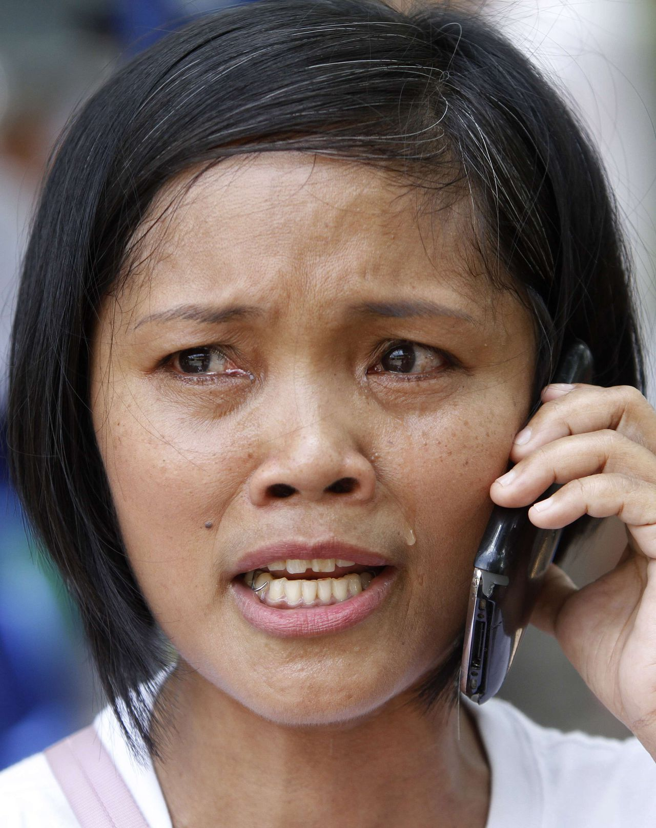 Gina Tubo, a supporter of Filipino boxer Manny Pacquiao, cries as she is being interviewed over the phone by a reporter following Pacquiao's loss to Timothy Bradley Jr. of the U.S., during a free viewing of the fight in Marikina City, Metro Manila June 10, 2012. Pacquiao was stunned by American Bradley on Saturday, surrendering his WBO welterweight title on a controversial split decision at the MGM Grand Garden Arena. It was Pacquiao's first defeat since he lost to Erik Morales in Las Vegas in March 2005, ending a run of 15 consecutive wins by the Filipino who has won world titles in an unprecedented eight weight divisions. REUTERS/Cheryl Ravelo (PHILIPPINES - Tags: SPORT BOXING TPX IMAGES OF THE DAY)