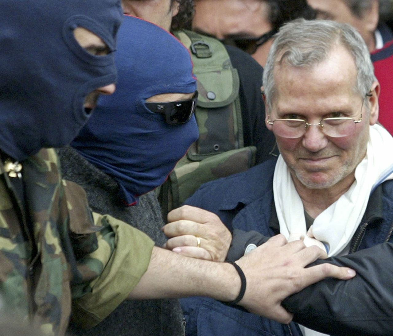 Bernardo Provenzano, die 43 jaar voortvluchtig was, na zijn arrestatie. (Foto Reuters) Italian police officers lead Sicilian Mafia boss Bernardo Provenzano (R) from a police station in the southern city of Palermo April 11, 2006. Provenzano, the undisputed chief of the Sicilian Mafia who had been on the run for more than four decades, was arrested while hiding in a farmhouse near Corleone in Sicily on Tuesday, officials said. REUTERS/Marcello Paternostro