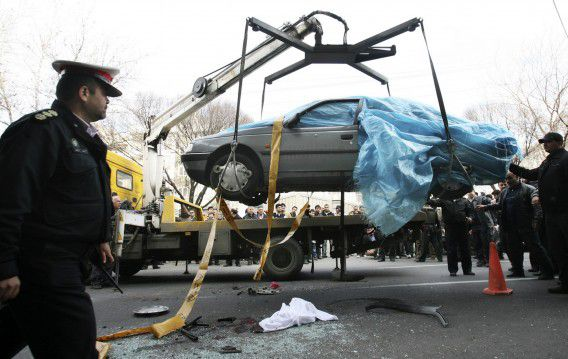 In this photo provided by the semi-official Fars News Agency, people gather around a car as it is removed by a mobile crane in Tehran, Iran, Wednesday, Jan. 11, 2012. Two assailants on a motorcycle attached magnetic bombs to the car of an Iranian university professor working at a key nuclear facility, killing him and wounding two people on Wednesday, a semiofficial news agency reported. (AP Photo/Fars News Agency, Mehdi Marizad)