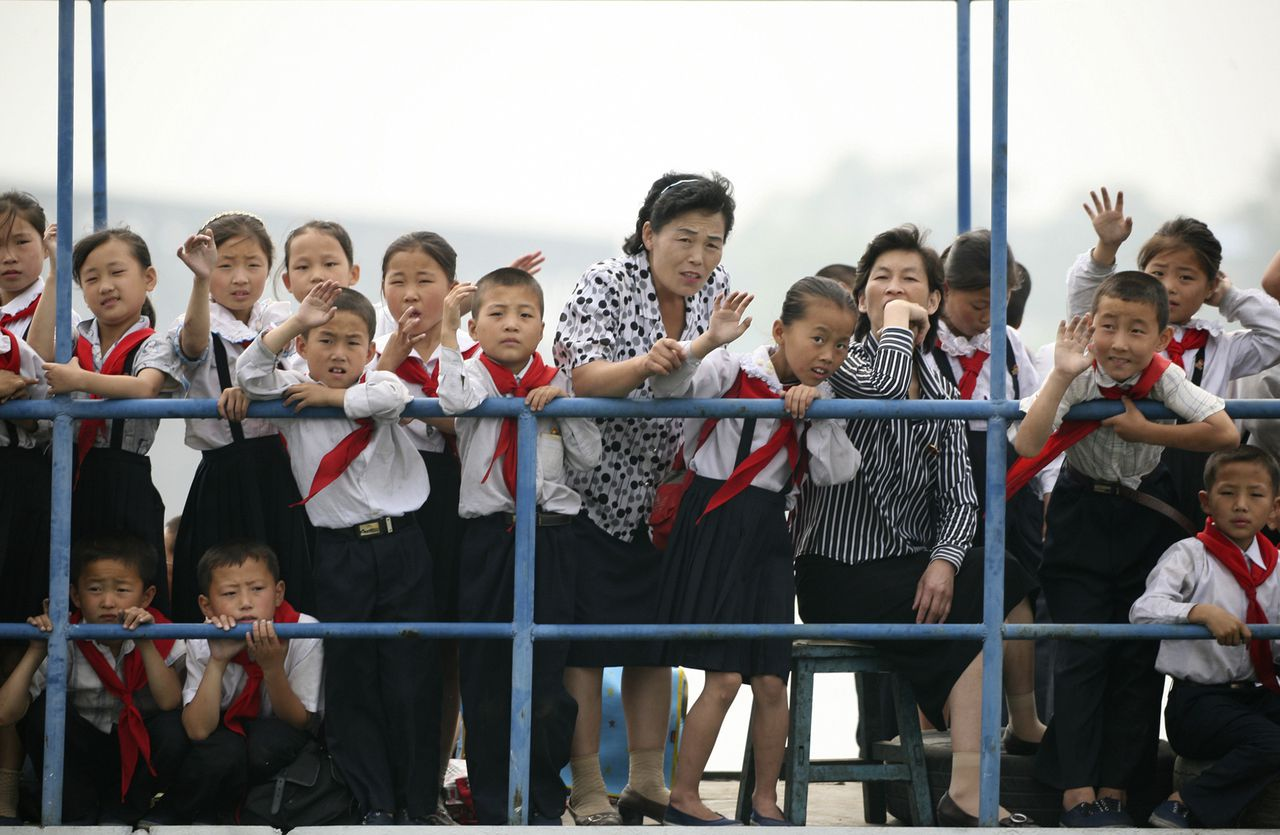 Noord-Koreaanse kinderen zwaaien naar Chinese toeristen op een boot op de grensrivier Yalu. Foto Reuters North Korean children wave to a Chinese tourist boat on the Yalu River near the North Korean town of Sinuiju, opposite the Chinese border city of Dandong, July 4, 2009. North Korea test-fired four missiles on Saturday, South Korea's defence ministry said, in an act of defiance towards the United States that further stoked regional tensions already high due to its nuclear test in May. REUTERS/Jacky Chen (NORTH KOREA POLITICS MILITARY)