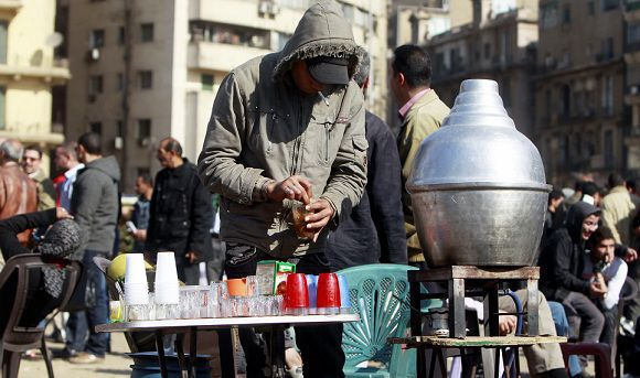 Caption: A street vendor sells hot drinks during a sit-in against military rule at Tahrir Square in Cairo December 22, 2011. The Muslim Brotherhood, whose party is leading Egypt's staggered parliamentary election, came out on Thursday against bringing forward a presidential vote to end military rule, saying changing the timetable would wreak chaos. Protesters who fought soldiers and police in central Cairo for five days before calm was restored this week want the army to cede power more swiftly. REUTERS/Amr Abdallah Dalsh (EGYPT - Tags: CIVIL UNREST POLITICS)