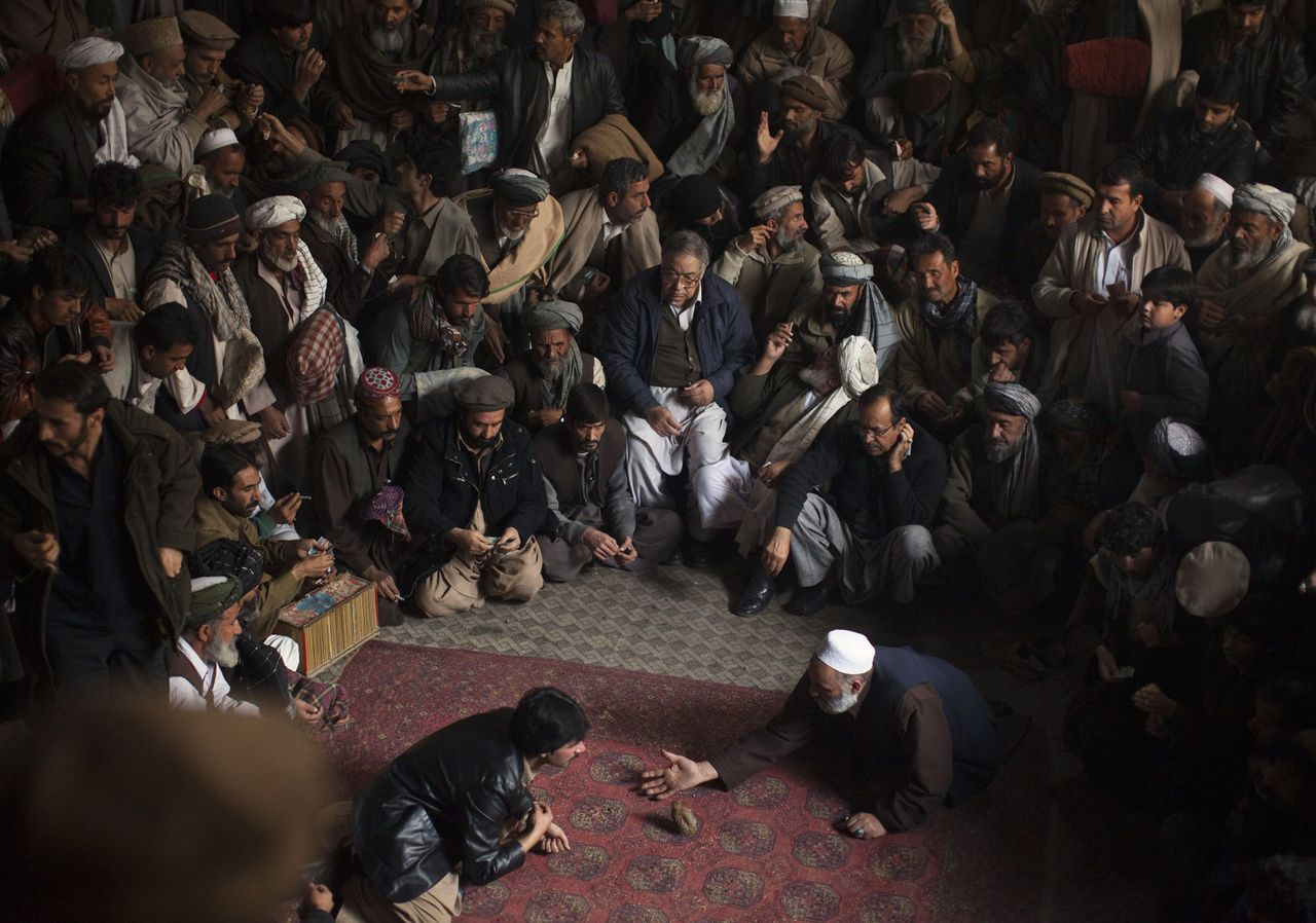 Men watch a quail fighting competition in Kabul November 24, 2011. Quail fighting is both a popular hobby and a gambling game for people in Afghanistan. REUTERS/Ahmad Masood (AFGHANISTAN - Tags: SOCIETY ANIMALS TPX IMAGES OF THE DAY)