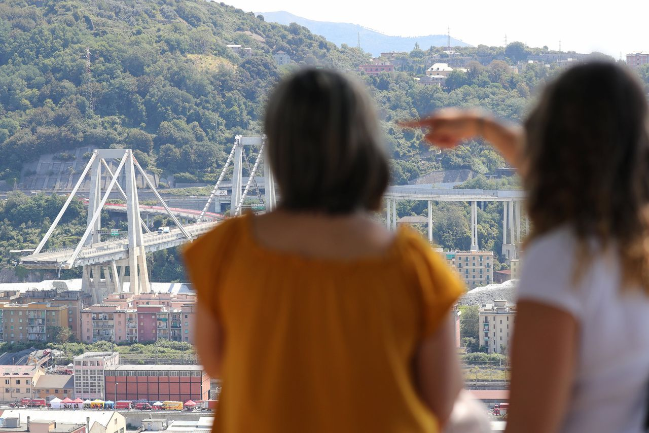 Twee vrouwen wijzen naar de ingestorte Ponte Morandi.