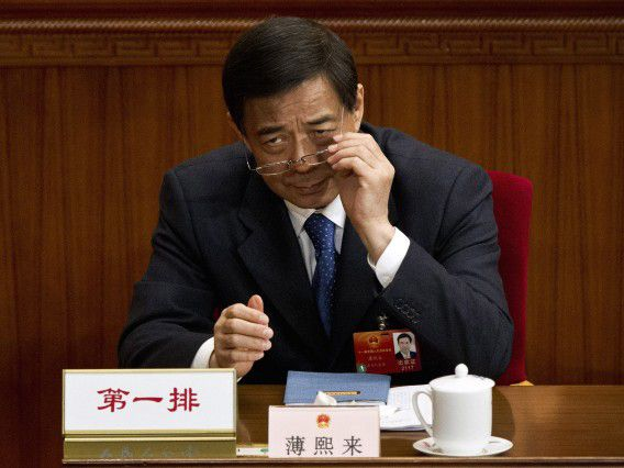 FILE - In this March 11, 2012 file photo, then-Chongqing party secretary Bo Xilai puts on his glasses during a plenary session of the National People's Congress at the Great Hall of the People in Beijing. Disgraced Chinese politician Bo was expelled from the ruling Communist Party on Friday, Sept. 28, 2012, and will face corruption and other criminal charges, the latest step in a scandal that has overshadowed a political transition now set to take place in early November. (AP Photo/Andy Wong, File)