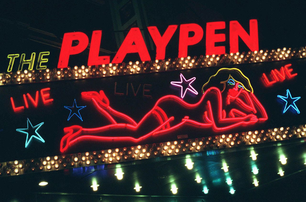 Stripclub op Times Square in New York. De Amerikaanse seksindustrie heeft de omzet zien dalen sinds de economie in een recessie terecht is gekomen. (Foto AP) A detail from a sign above a strip club in New York's Times Square advertises The Playpen Friday evening, March 6, 1998, after a judge concluded the city has the legal right to force most of the city's X-rated shops to relocate. Judge Miriam Goldman Cedarbaum, said she would stay her ruling until Wednesday to allow sex shop owners to appeal to the 2nd U.S. Circuit Court of Appeals to stop the city's plan. (AP Photo/Michael Schmelling)