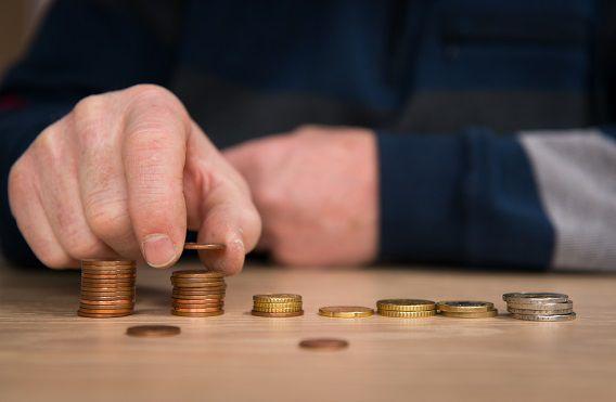 Een gepensioneerde automonteur telt de muntjes uit zijn portemonnee.