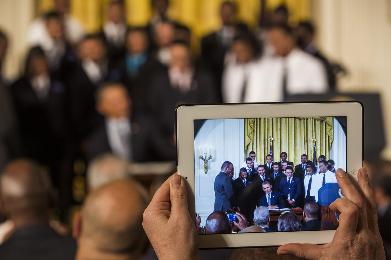 epa04103073 US President Barack Obama, surrounded by students from a Chicago youth guidance program called Becoming A Man, is seen in a crowd-member's iPad as he signs a Presidential Memorandum, called the My Brother's Keeper Task Force, in the East Room of the White House in Washington, DC, USA, 27 February 2014. The initiative is aimed at providing opportunities for young black and Hispanic men. EPA/JIM LO SCALZO