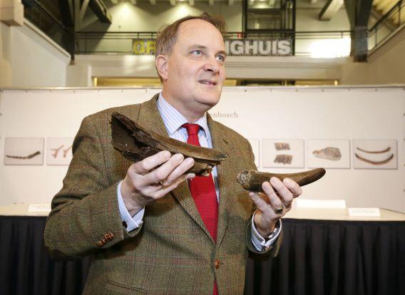 Wethouder Huib van Olsen toont een mammoetslagtand gevonden in Den Bosch