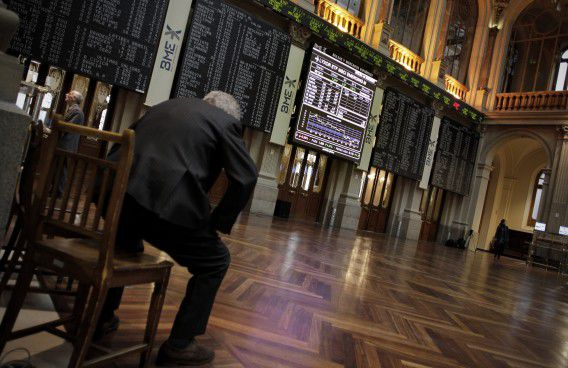 A broker stands up in front of the main display at the Stock Exchange, in Madrid, Friday, Dec. 2, 2011. General election winner Mariano Rajoy is due to take office as prime minister Dec. 21. He is expected to introduce severe economic reforms in a bid to reboot the ailing economy. (AP Photo/Alberto Di Lolli)