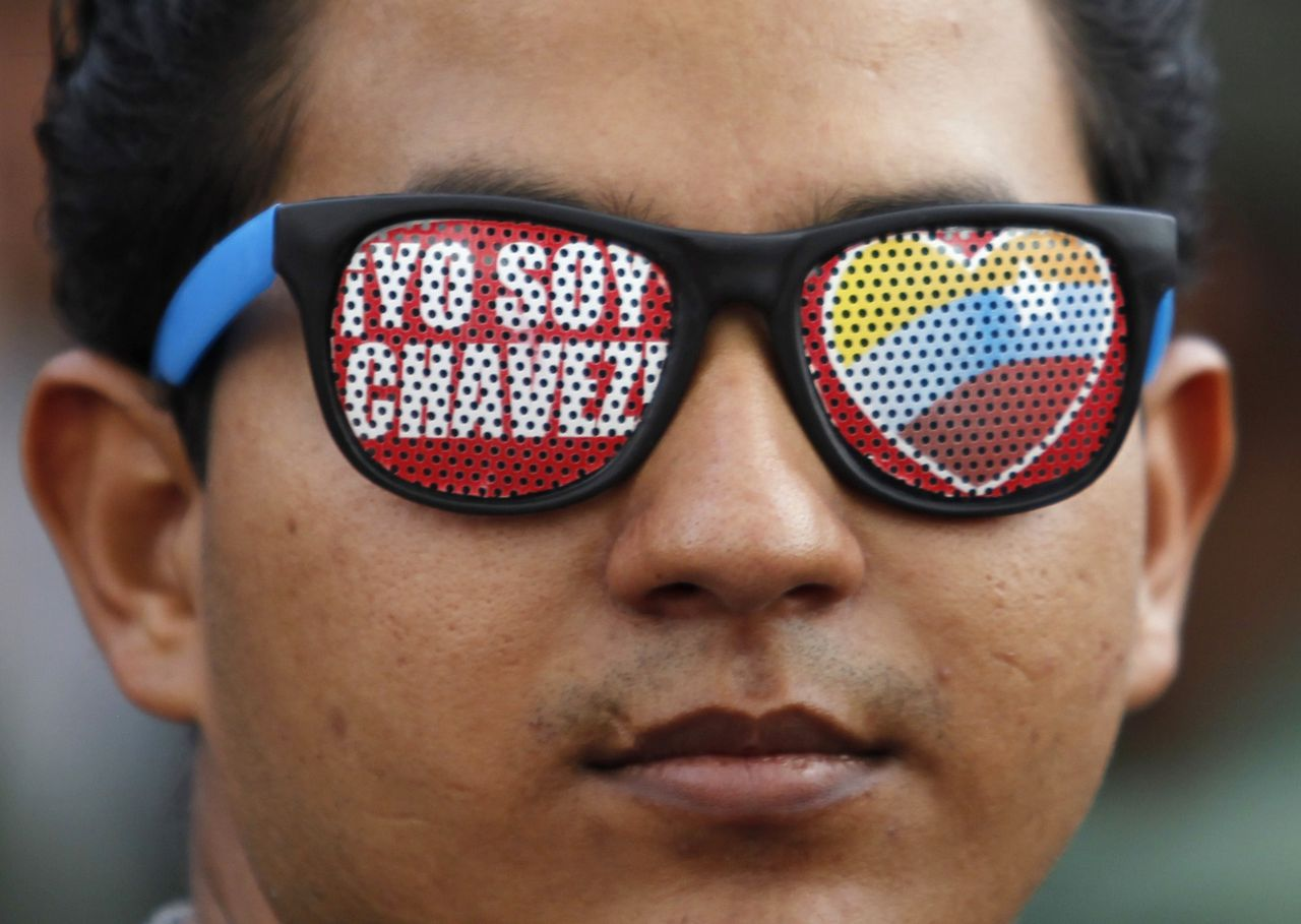 """A supporter of Venezuela's President Hugo Chavez wears glasses reading """"I'm Chavez"""" as he attends a parade to commemorate the 21st anniversary of Chavez's attempted coup d'etat in Caracas February 4, 2013. Chavez is still in Cuba recovering from a cancer surgery and has not been seen in public since December 8 last year. REUTERS/Carlos Garcia Rawlins (VENEZUELA - Tags: POLITICS ANNIVERSARY)"""