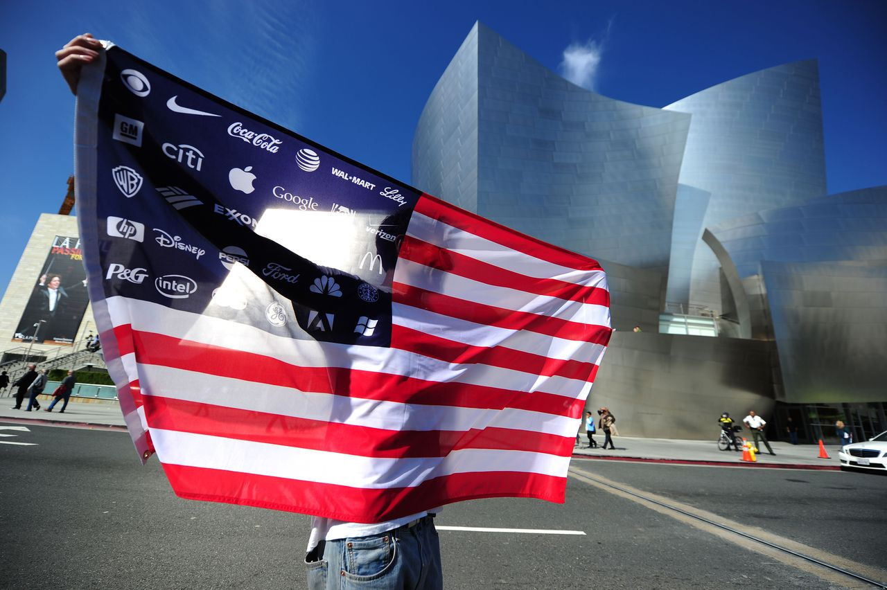 "An Occupy LA protestor holds a US flag with the names of large corporations printed on it, during a march through the downtown Los Angeles financial district on ""Bank Transfer Day,"" November 5, 2011. Bank Transfer Day, created by the Occupy movement, is a national effort to get people to move their money from large corporate banks into smaller banks or credit unions. TOPSHOTS AFP PHOTO / Robyn Beck"