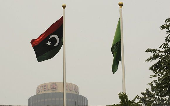 """Caption: The flag (L) of the Libyan transitional government flies at the Libyan Embassy in Beijing on August 23, 2011. China urged the continuation of """"mutually beneficial"""" trade ties with oil-rich Libya, after rebels trying to end Moamer Kadhafi's 42-year rule stormed the capital Tripoli. AFP PHOTO / Peter PARKS"""