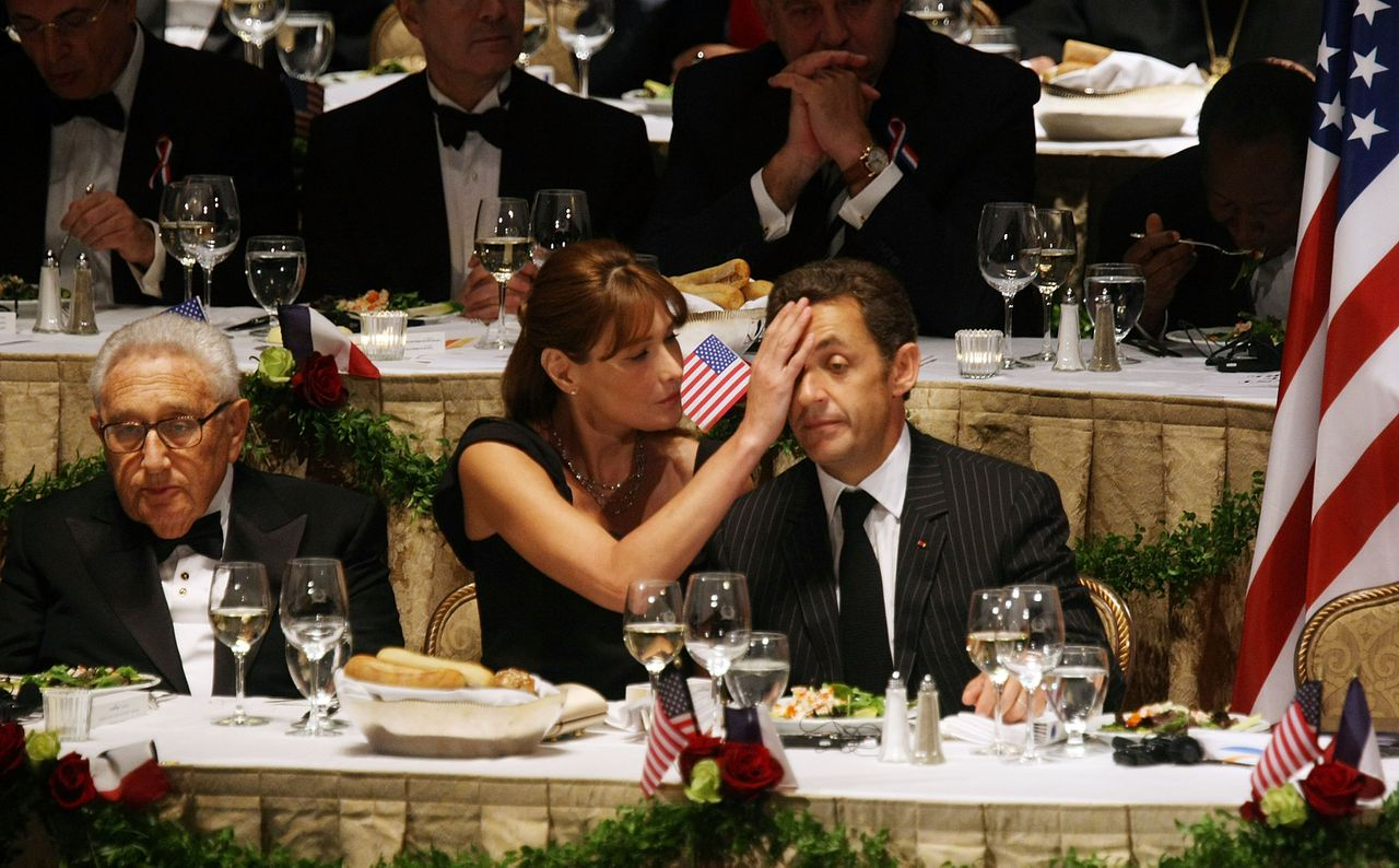"""De Amerikaanse oud-minister van Buitenlandse Zaken Henry Kissinger, Carla Bruni en haar echtgenoot, de Franse president Nicolas Sarkozy in New York, VS, 23 september 2008 Foto Getty Images, AFP (R to L) French President Nicolas Sarkozy, wife Carla Bruni Sarkozy and former Secretary of State Henry Kissinger attend the 2008 Appeal of Conscience Foundation awards dinner at the Waldorf-Astoria hotel September 23, 2008 in New York City. Sarkozy was presented with the Appeal of Conscience World Statesman Award for """"his leadership in advancing freedom, tolerance and inter-religious understanding."""" Mario Tama/Getty Images/AFP == FOR NEWSPAPERS, INTERNET, TELCOS & TELEVISION USE ONLY == == FOR NEWSPAPERS, INTERNET, TELCOS & TELEVISION USE ONLY =="""