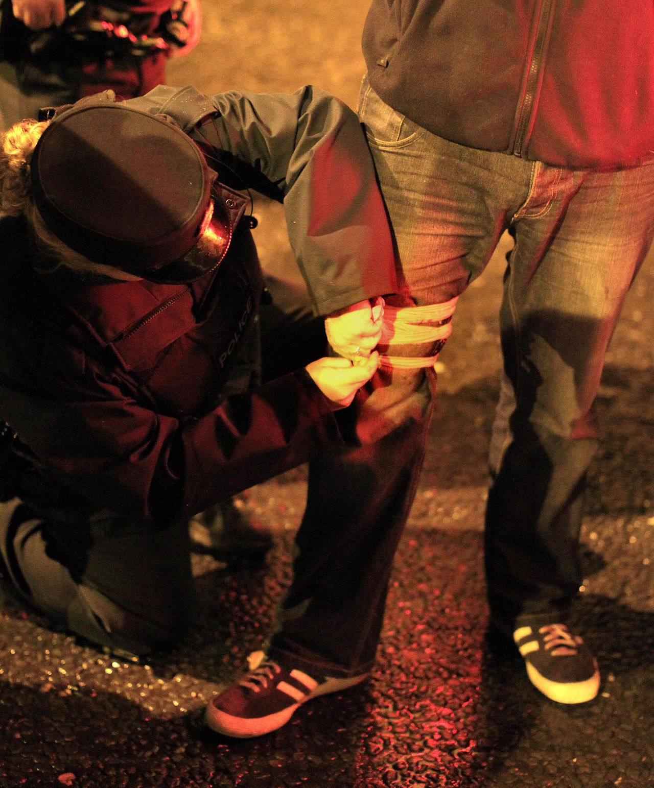 A Northern Ireland police officer puts a bandage on a press photographer's leg after he was shot by a rioter in East Belfast, Northern Ireland, Wednesday, June 22, 2011. Rioting began for the second night between Catholic and Protestant gangs. (AP Photo/Peter Morrison)