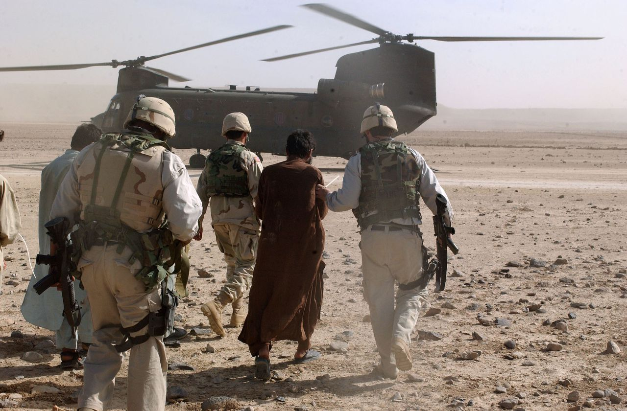 """Amerikaanse militairen voeren een Afghaanse terreurverdachte af naar een helikopter, in april 2003. (Foto AP) U.S. Army Criminal Investigation Task Force members escort an Afghan detainee aboard a C-47 """"Chinook"""" helicopter as part of """"Operation Resolute Strike"""" in Sangin, Afghanistan, Wednesday, April 9, 2003. """"Operation Resolute Strike"""" which concluded Wednesday, was conducted based on intelligence from ambush that left two U.S. service members dead and one seriously injured March 29. (AP Photo/U.S. Military, Spc. Jim Wagner, HO)"""