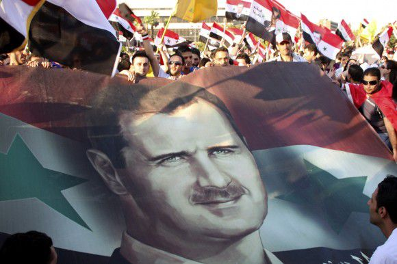 Syrians carry national flags and a picture of Syrian President Bashar Assad as they protest in his support at the Umayyad Square in downtown Damascus, Syria, Sunday, July 17, 2011. The rally is held to mark the 11th anniversary of Assad's swearing-in ceremony and to voice allegiance and loyalty to their leader whose country has been plagued by four months of protests. (AP Photo/ Bassem Tellawi)