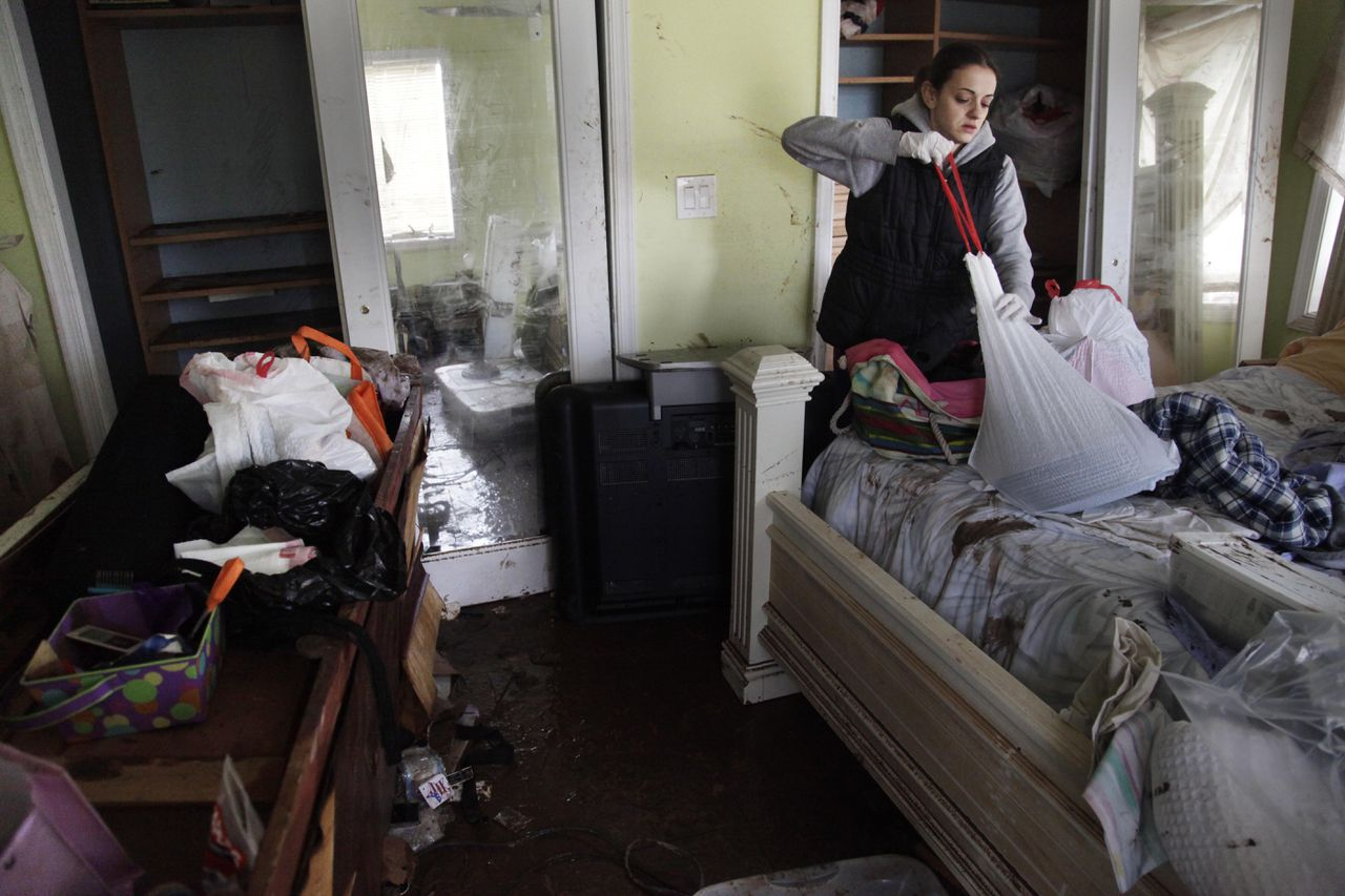 Brooke Clarkin tries to salvage some personal items from her mother's home in Staten Island, New York, Thursday, Nov. 1, 2012. Her mother's home was not only flooded to the ceiling, but was swept off its foundation and was carried to the other side of the street. The National Guard and federal emergency management officials will deliver 1 million meals and bottled water to New York areas hardest hit by Superstorm Sandy. (AP Photo/Seth Wenig)