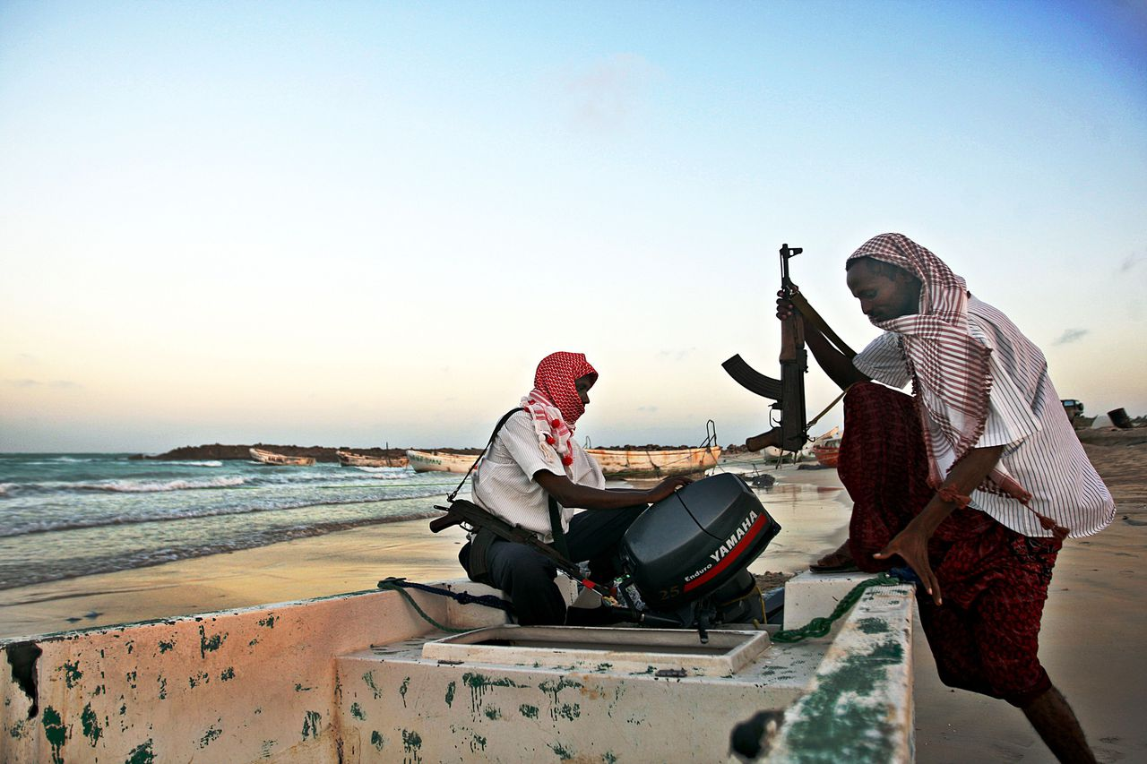 """(FILES) Photo taken on January 4, 2010 shows armed Somali pirates carrying out preparations to a skiff in Hobyo, northeastern Somalia, ahead of new attacks on ships sailing in the Gulf of Aden. Pirates holding ships just off the Somali town of Harardhere moved them on May 3, 2010 after Islamist militants seized the town, residents and pirates said. """"The Islamists have not interfered with us yet but some ships near Harardhere were moved in order to avoid any attempt to interfere,"""" Abdi Yare, a pirate in the nearby coastal town of Hobyo, another pirate hub, told AFP. AFP PHOTO FILES / MOHAMED DAHIR"""