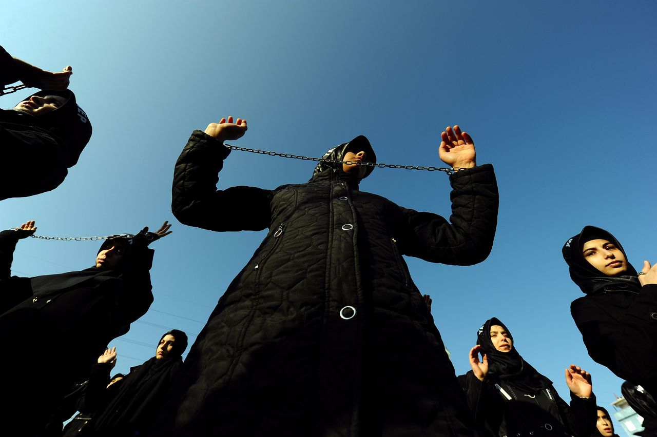 Turkish Shiite women with chains take part in a religious procession held for Ashura in Istanbul on December 5, 2011. Ashura commemorates the killing of Imam Hussein, a grandson of the Prophet Mohammed, by armies of the caliph Yazid in 680 AD. Tradition holds that the revered imam was decapitated and his body mutilated in the Battle of Karbala. AFP PHOTO/ MUSTAFA OZER