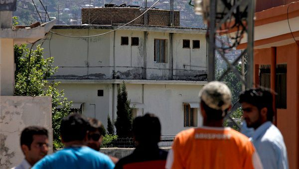 Caption: Pakistani youths view the house, background, of former al-Qaida leader Osama bin Laden in Abbottabad, Pakistan on Sunday, May 8, 2011. Osama bin Laden was killed by a helicopter-borne U.S. military force on Monday, in a fortress-like compound on the outskirts of Pakistani city of Abbottabad. (AP Photo/Anjum Naveed)