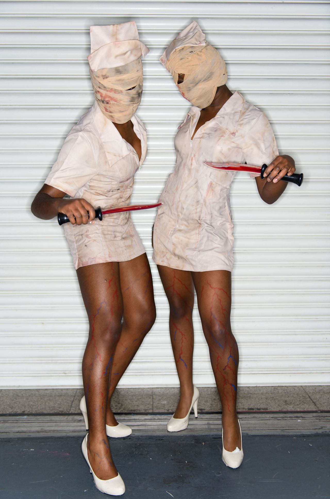 """""""Osato"""" and """"Ades"""" pose in their """"Silent Hill"""" nurse costumes during the London Comic Con event at the ExCel centre in east London on October 28, 2012. AFP PHOTO / LEON NEAL"""