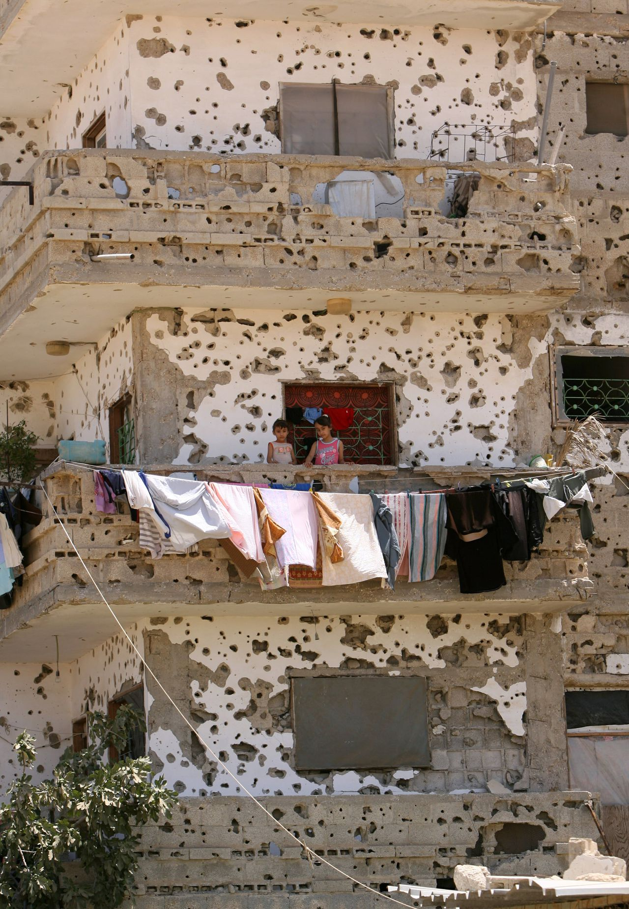 "Palestijnse meisjes staan op het balkon van hun beschoten huis in Rafah in de Gazastrook. (Foto AFP) Palestinian girls stand on the balcony of the ruined house, hit during Israel?s 22-day offensive over Gaza, on July 02 2009 in Rafah, southern Gaza Strip. Amnesty International said Israel inflicted ""wanton destruction"" in the Gaza Strip in attacks that often targeted Palestinian civilians during an offensive in December and January in the Hamas-run enclave. The London-based human rights group also accused Hamas of war crimes, but said it found no evidence to support Israeli claims that Gaza's Islamist rulers used civilians as human shields during Israel's massive 22-day offensive. AFP PHOTO/ SAID KHATIB"