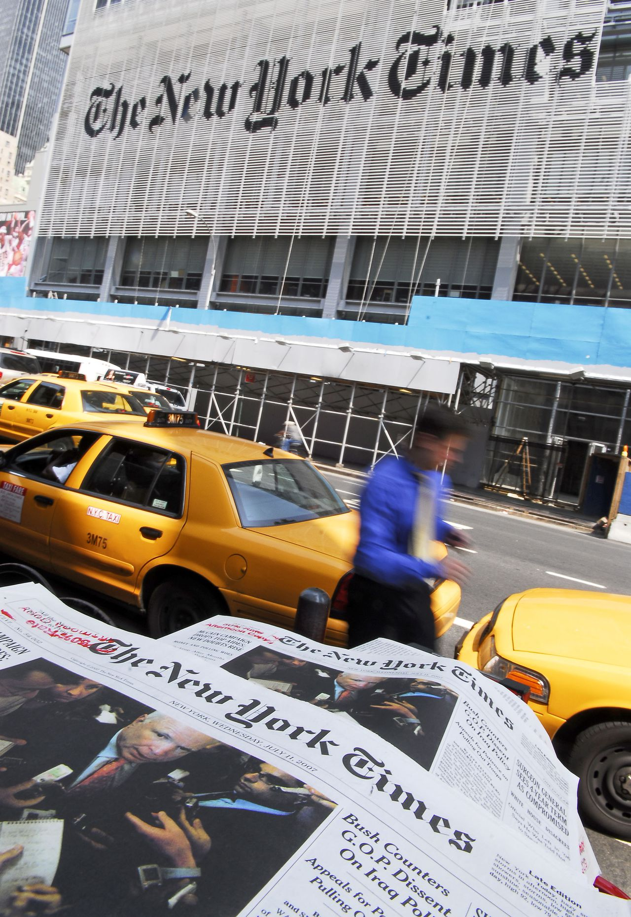 A pedestrian walks past copies of The New York Times that are displayed for sale across the street from The New York Times Building in New York, July 11, 2007. News Corp. Chairman Rupert Murdoch said he will take on the New York Times once his purchase of Dow Jones & Co. is complete by expanding non-business coverage at the Wall Street Journal. Photographer: Andrew Burton/Bloomberg News