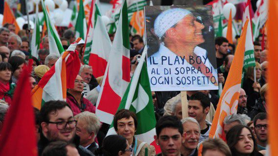 """Demonstrators hold a placard with a portrait of Italian Prime Minister Silvio Berlusconi and reading """"The playboy above suspicion"""" during a protest untitled """"Reconstruction. In the name of the Italian people"""" organized by the left-wing Democratic Party (PD) on November 5, 2011 in Rome. AFP PHOTO / ALBERTO PIZZOLI"""