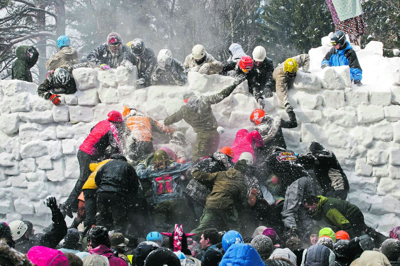 People storm a snow castle during celebrations of Maslenitsa, or Shrovetide, outside Marfino village, some 52 kilometers (32 miles) north of Moscow, Sunday, March 17, 2013. Maslenitsa is a traditional Russian holiday marking the end of winter that dates back to the pagan times. (AP Photo/Yevgeny Feldman)