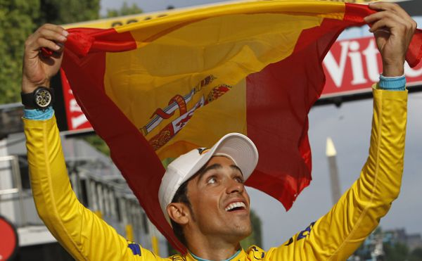 In this July 25, 2010 file photo, three-time Tour de France winner Alberto Contador of Spain holds aloft the Spanish national flag during a victory lap after winning the the Tour de France cycling race in Paris, France. The Spanish cycling federation cleared Alberto Contador of doping on Tuesday Feb. 15, reversing its proposal to ban him for one year for a positive test at the Tour de France. (AP Photo/Christophe Ena, File)