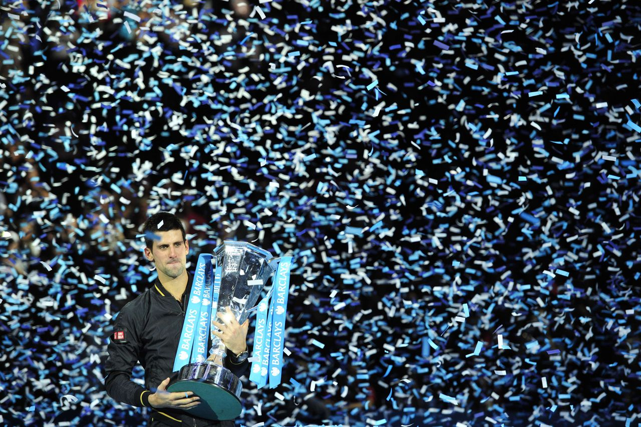 Serbia's Novak Djokovic poses with the winners' trophy after the singles final against Switzerland's Roger Federer on the eighth day of the ATP World Tour Finals tennis tournament in London on November 12, 2012. AFP PHOTO / GLYN KIRK