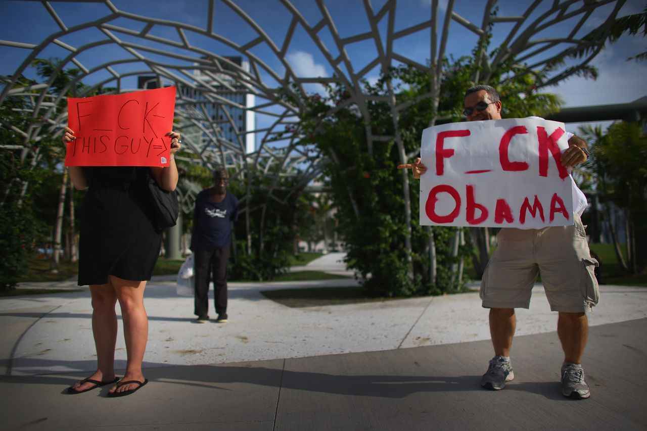 """MIAMI BEACH, FL - JUNE 26: Alexis Murphy (L) holds a sign reading, """" F_ck this Guy"""" as she points it at Jerry Gonzalez who stands near her holding a sign reading, """" F_ck Obama"""", as they stand outside a President Barack Obama fundraiser at the Fillmore Miami Beach at Jackie Gleason Theater on June 26, 2012 in Miami Beach, Florida. President Obama was in Miami Beach to continue his campaign for another four year term. Joe Raedle/Getty Images/AFP == FOR NEWSPAPERS, INTERNET, TELCOS & TELEVISION USE ONLY =="""