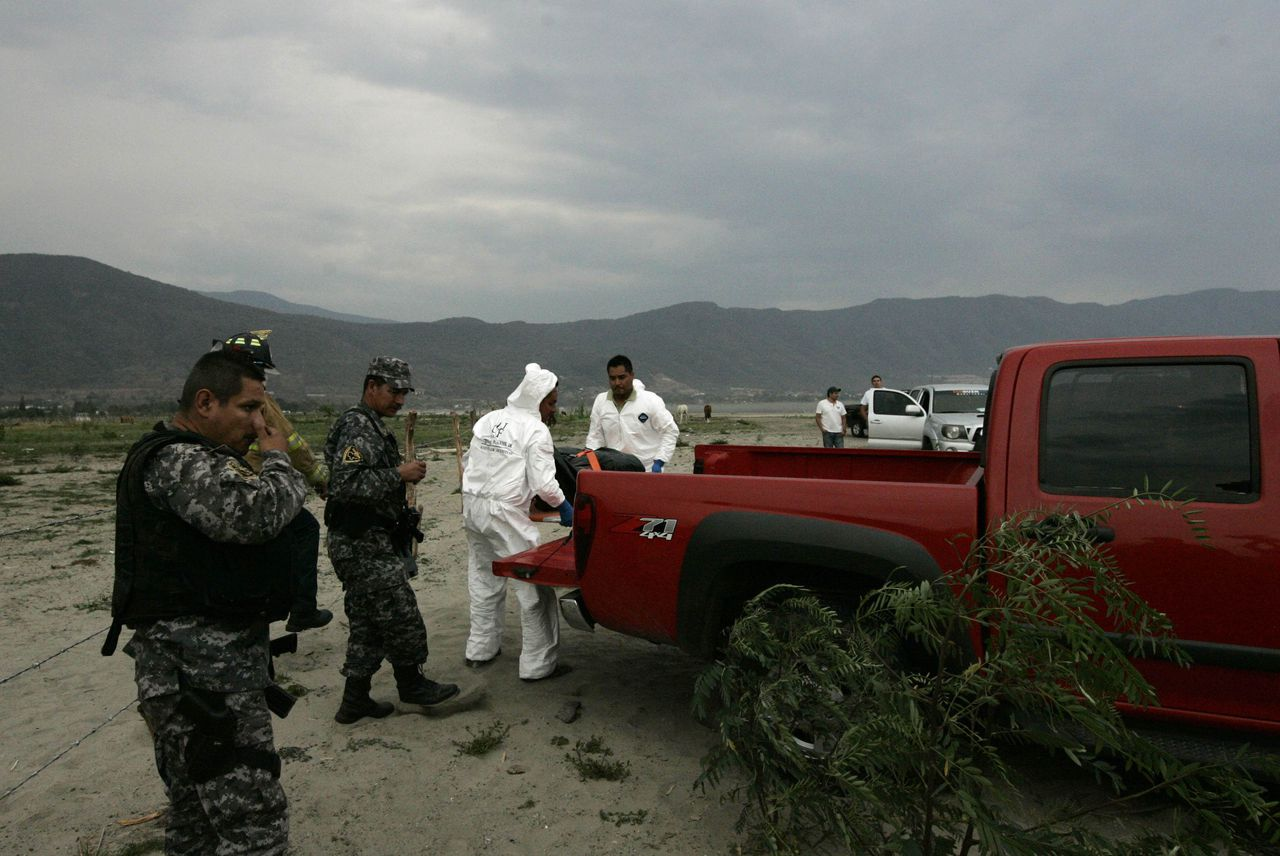 Forensic technicians carry the slain body of a man found at a clandestine grave near Chapala lake in Jocotepec June 9, 2012. For decades, American and Canadian expats have flocked to the shores of Chapala, seeking refuge in the spring-like climate of Mexico's largest natural lake, where English author D.H. Lawrence once came for inspiration. But the calm of the clustered lakeside retreats was shattered in May 2012 when suspected drug-gang hitmen kidnapped a group of Mexican locals and dumped 18 decapitated bodies in two vehicles just miles (kilometres) from the lakeside tourist enclave of Ajijic. Picture taken June 9, 2012. REUTERS/Alejandro Acosta (MEXICO - Tags: CIVIL UNREST CRIME LAW DRUGS SOCIETY)