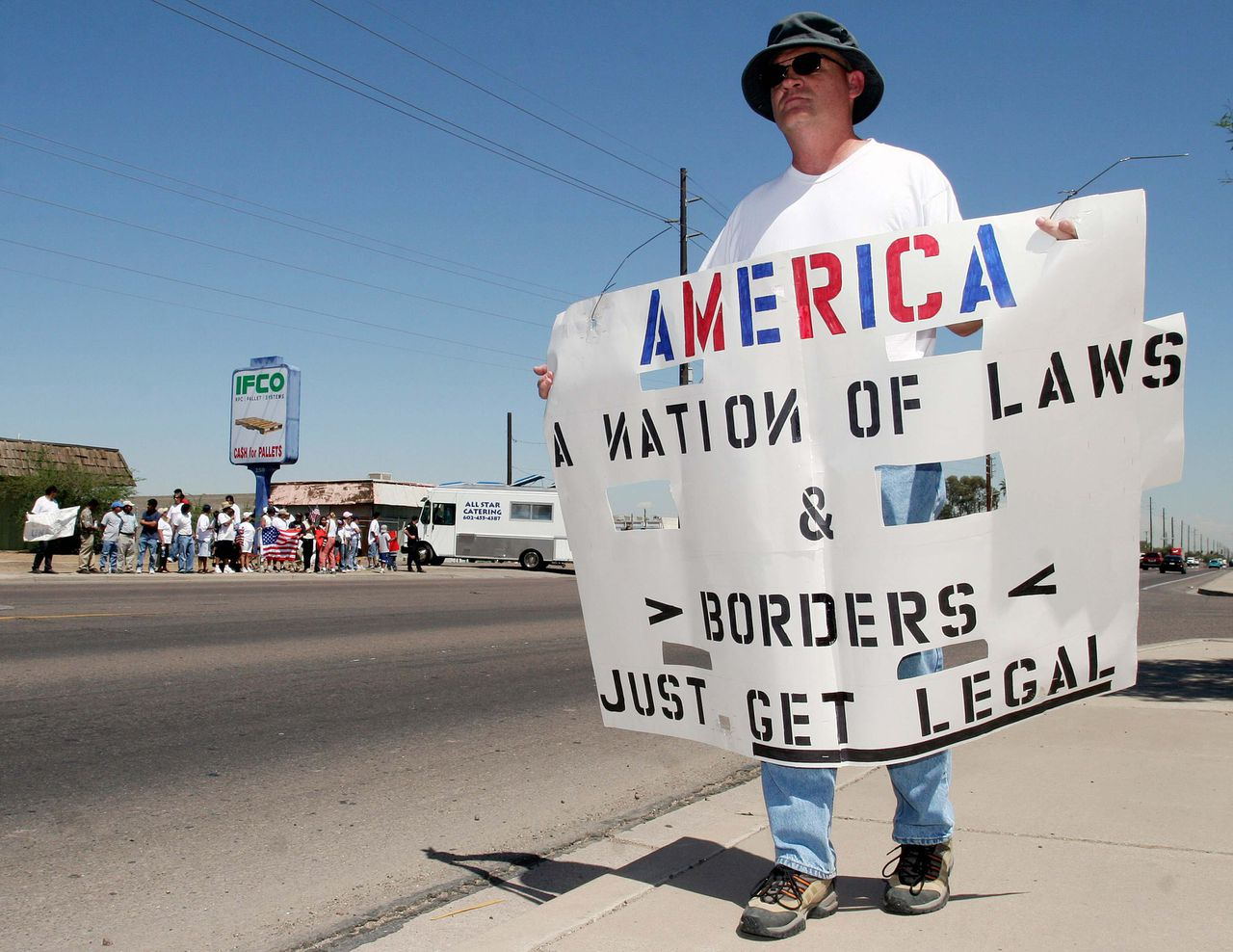 Demonstratie voor een filiaal van Ifco in Phoenix, Arizona. Foto Reuters Een man in Phoenix, Arizona protesteert tegen demonstranten die voor een kantoor van Ifco Systems betogen tegen de arrestatie van 25 werknemers zonder papieren. Foto Reuters Barry Statesman, of Phoenix, counter protests immigration rights protestors (in background) outside the offices of IFCO Systems during a rally in Phoenix, Arizona May 1, 2006. Thirty-five undocumented workers were arrested at IFCO's Phoenix office on April 19 as part of a nationwide raid in which almost 1,200 were arrested. From the streets of New York to the lettuce fields of California, hundreds of thousands of immigrants left their jobs, shunned business as usual and marched in a powerful bid to legitimize millions of workers now in the United States illegally. REUTERS/Jeff Topping
