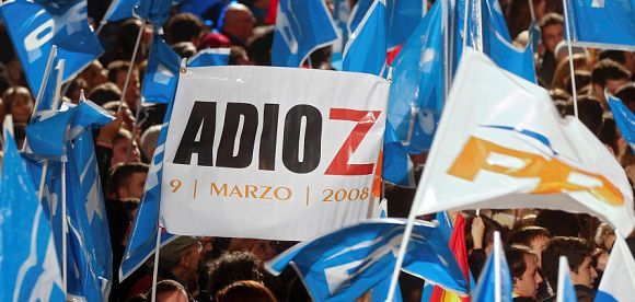 """Caption: People's Party (Partido Popular) supporters wave flags and a banner reading """"Adioz"""" spelled incorrectly with a Z, a reference to Spain's Prime Minister Jose Luis Rodriguez Zapatero, as they gather outside the party headquarters to wait for the results of Spain's general elections in Madrid, November 20, 2011. Spain's centre-right People's Party was heading to a landslide victory in Sunday's parliamentary election, taking 44 percent of the vote, or 187 seats in the lower house, with 78 percent of polling stations counted. REUTERS/Sergio Perez (SPAIN - Tags: POLITICS ELECTIONS)"""