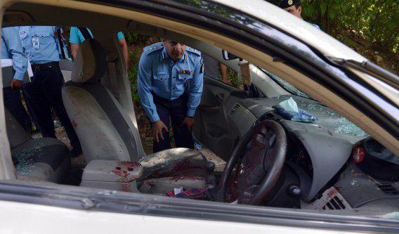 Pakistaanse politieagenten onderzoeken de met kogels doorzeefde auto van aanklager Chaudhry Zulfiqar.