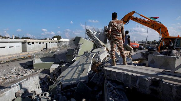 """Caption: Revolutionary fighters use heavy machinery to tear down a guard tower at the Bab al-Aziziya compound in Tripoli, Libya, Sunday, Oct. 16, 2011. Libyans using bulldozers have begun tearing down the walls surrounding Moammar Gadhafi's main Tripoli compound, known as Bab al-Aziziya. Ahmad Ghargory, the commander of a revolutionary brigade, says forces had been busy with the war but now it's time """"to tear down this symbol of tyranny."""" He says the area will be turned into a public park. The compound has long been seen as the symbolic heart of Gadhafi's rule. (AP Photo/Abdel Magid al-Fergany)"""