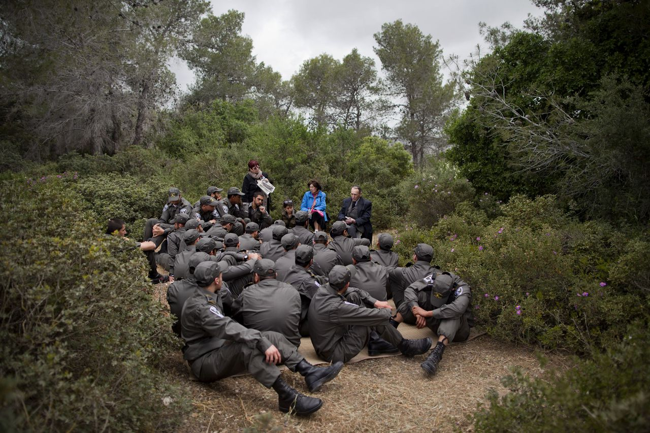 Holocaust survivor Meir Friedman, center right, tells his personal testimony to Israeli border police officers during a ceremony marking the annual Holocaust remembrance day a in the Martyr's forest near Moshav Kesalon, in central Israel, Thursday, April 19, 2012. Sirens sounded across Israel on Thursday morning, bringing life to a standstill as millions of Israelis observed a moment of silence to honor the memory of the 6 million Jews killed in the Holocaust of World War II. (AP Photo/Oded Balilty)