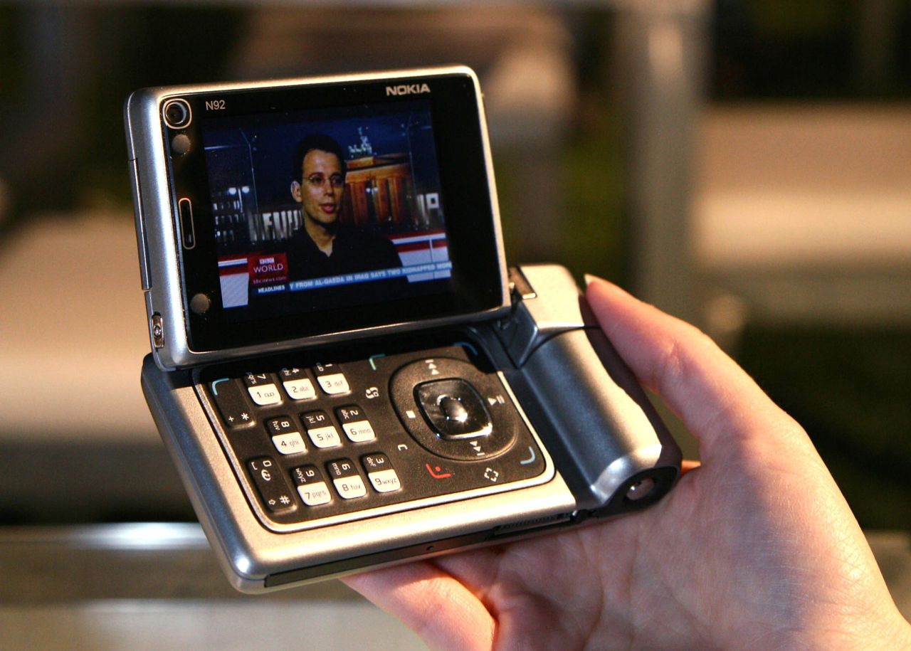 Stichting KijkOnderzoek wil meten hoe vaak mensen tv kijken op een iPod of de mobiele telefoon. Foto Reuters An undated handout photo shows a Nokia N92, the world's first dedicated mobile TV device. Trials of Digital Video Broadcast-Handheld (DVB-H) -- an industry standard which allows an unlimited number of handsets to receive broadcast television -- mainly aims to test technical capabilities. Many believe consumer interest is guaranteed. Nokia's N92 handset, which some analysts say will open this market, is expected to hit the shelves later this year and is designed for TV viewers. To match feature Tech-Mobiletv REUTERS/Nokia/Handout