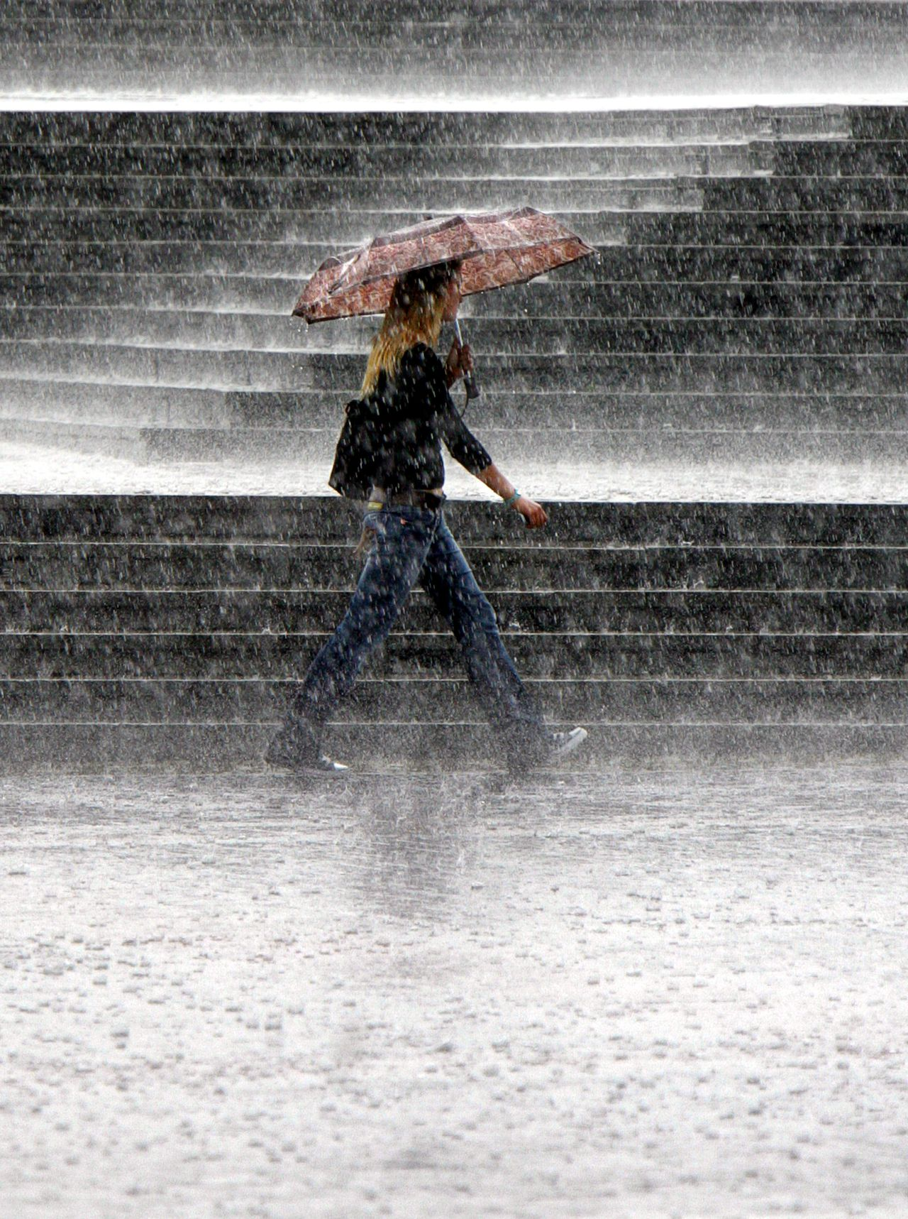 A girl walks during a downpour in central Moscow, 25 August 2006. AFP PHOTO / VIKTOR DRACHEV.