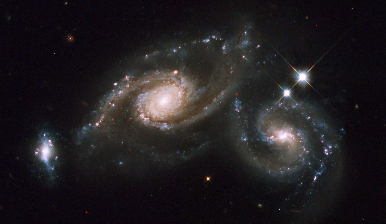 Foto AP Photo/ Hubble Space Telescope/NASA Foto Arp 247 'mooist' On April 1-2, the Hubble Space Telescope photographed a group of galaxies called Arp 274. Arp 274, also known as NGC 5679, is a system of three galaxies that appear to be partially overlapping in the image, although they may be at somewhat different distances. The spiral shapes of two of these galaxies appear mostly intact. The third galaxy, to the far left, is more compact, but shows evidence of star formation. Two of the three galaxies are forming new stars at a high rate. This is evident in the bright blue knots of star formation that are strung along the arms of the galaxy on the right and along the small galaxy on the left. The entire system resides at about 400 million light-years away from Earth in the constellation Virgo. (AP Photo/ Hubble Space Telescope/NASA)