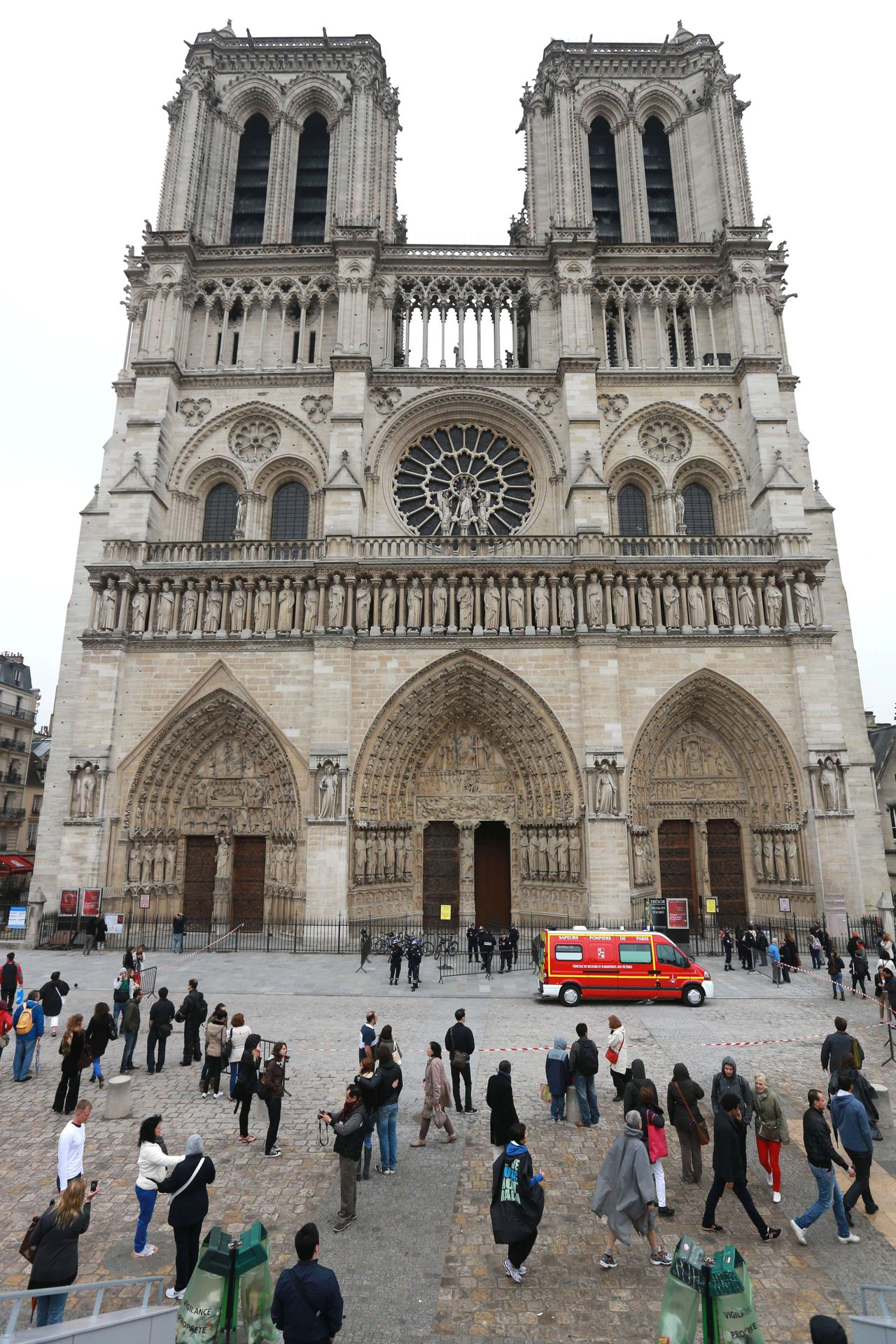 People gather while French policemen cordon off in front of Paris' Notre Dame Cathedral near a vehicle of French firefighters on May 21, 2013, following the evacuation of the cathedral after a man shot himself dead in front of the altar. The man, in his 70s, who was well-known far-right figure, committed suicide with a pistol some time after 1400 GMT, investigators said. AFP PHOTO / PIERRE VERDY