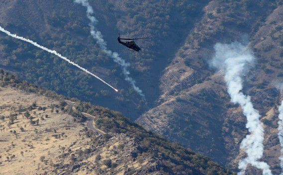 A Turkish military Cobra helicopter release flares over a mountain in Cukurca, near the Iraqi border in southeastern Turkey October 22, 2011. REUTERS/Osman Orsal (TURKEY - Tags: POLITICS MILITARY)