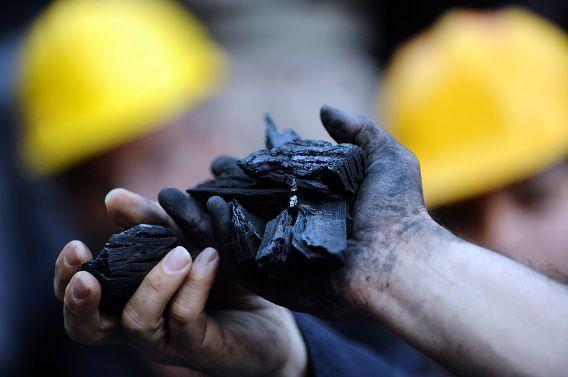 Demonstranten houden kolen in hun hand tijdens een demonstratie voor de slachtoffers van het mijnongeluk.