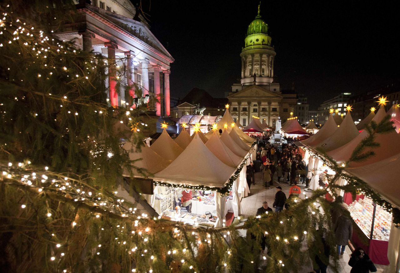 People stroll through the Christmas market during its opening day in Berlin's Gendarmenmarkt square November 21, 2011. REUTERS/Thomas Peter (GERMANY - Tags: SOCIETY TRAVEL)