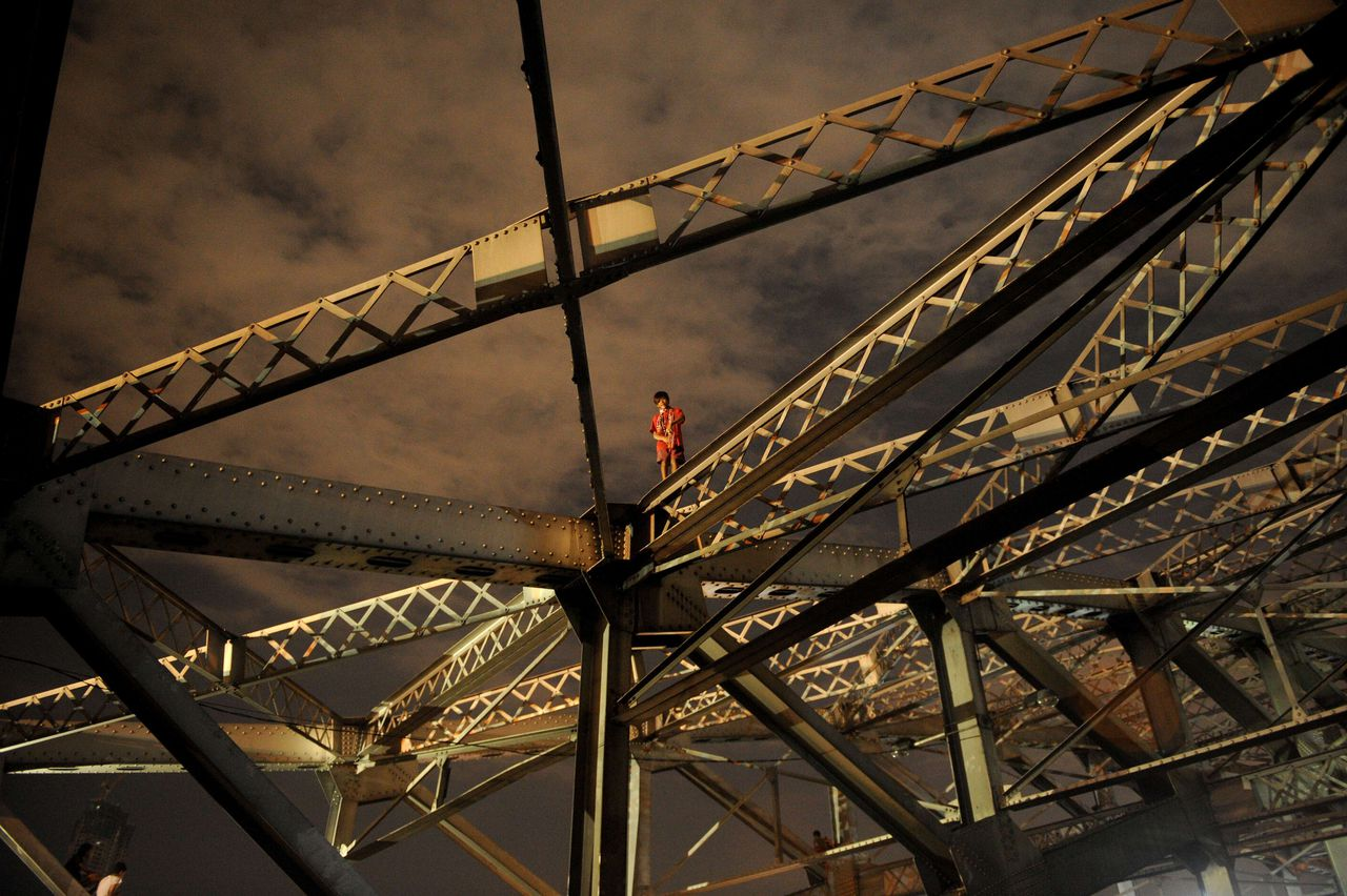 A homeless child stands on one of the trusses of the Quezon Bridge in Manila on January 27, 2013. Philippine President Benigno Aquino on December 19, 2012 signed into law a 2.005 trillion-peso (49 billion USD) budget for 2013, vowing to use higher taxes on tobacco and alcohol to boost programmes to reduce poverty, education, health, agriculture and a cash-transfer scheme for the poor are the key priorities of the appropriations, which are 10.5 percent higher than the 2012 national budget. AFP PHOTO/NOEL CELIS