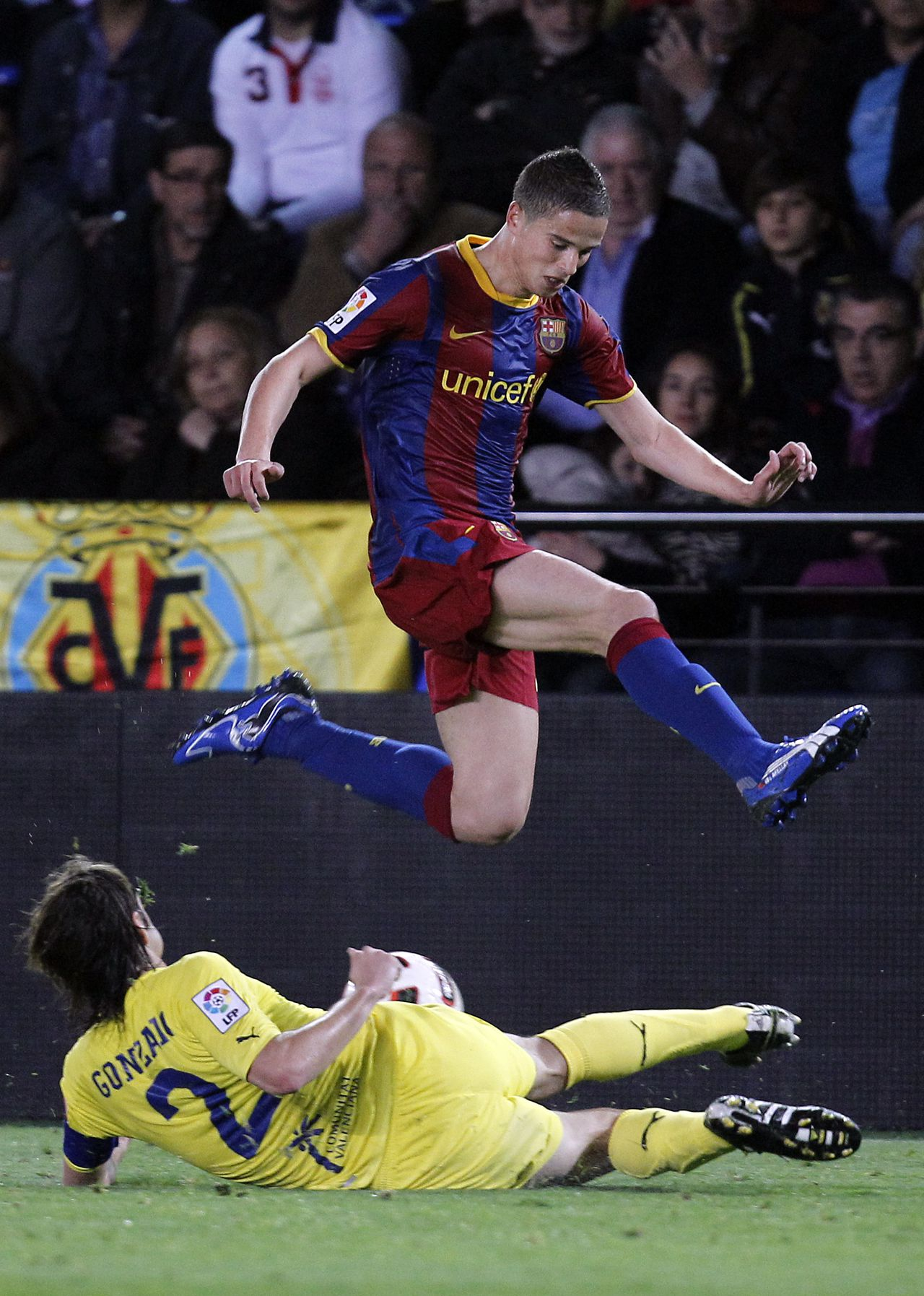 Barcelona's Ibrahim Afellay from Neetherlands, top, vies for the ball with Villarreal's Gonzalo Rodriguez, bottom, during their Spanish La Liga soccer match at Madrigal stadium in Villarreal, Saturday, April 2, 2011. (AP Photo/ Alberto Saiz)