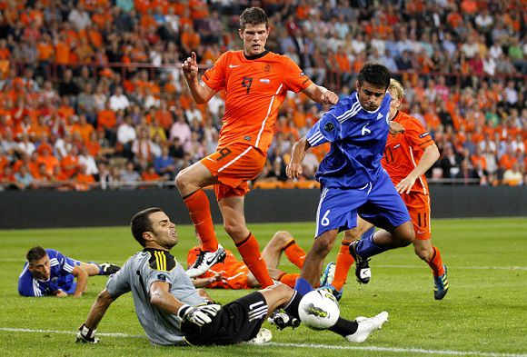 Caption: Dutch soccer player Klaas Jan Huntelaar, center, battle for the ball with goalkeeper Aldo Junior Simoncini and Giacomo Benedettini, right, of San Marino, during their Euro 2012 Group E qualifying soccer match between The Netherlands and San Marino at the Philips stadium in Eindhoven, The Netherlands, friday Sept. 2, 2011. (AP Photo/Bas Czerwinski)