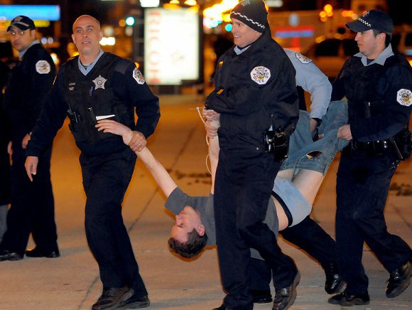 Caption: Chicago police carry away a protester at the Global Day of Occupation-Chicago March to Michigan and Congress, early Sunday, Oct. 16, 2011, in Chicago. Police arrested 175 members of a group protesting corporate greed early Sunday after they refused to take down their tents and leave a city park when it closed. (AP Photo/Chicago Sun-Times, Scott Stewart) CHICAGO LOCALS OUT; MAGS OUT